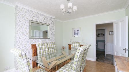 Beige and feature wallpaper wall dining room in cottage in Worlebury Hill Road, with glass table and six tartan chairs.