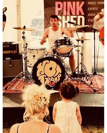 Daisy watching her dad Tom play the drums with Hot Tramp band