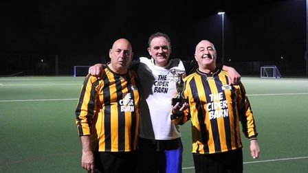 Shaun Palfrey of Pro Touch presents the trophy to Steve Henderson as Tim Richens looks on at Cheddar Walking Football Club