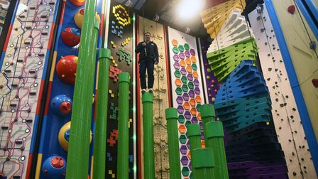 Man standing on green pole in front of backdrop of climbing walls