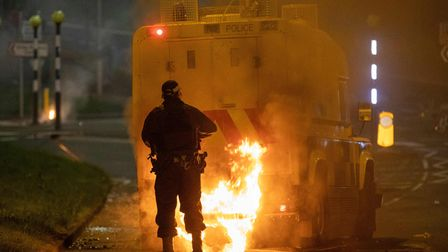 A police officer walks behind a police vehicle with flames leaping up the rear after violence broke out in Newtownabbey