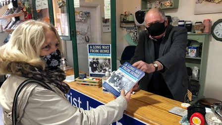 Community Rail volunteer Trevor Garrod sells a copy of A Long Way From Home at the Lowestoft Station Shop.