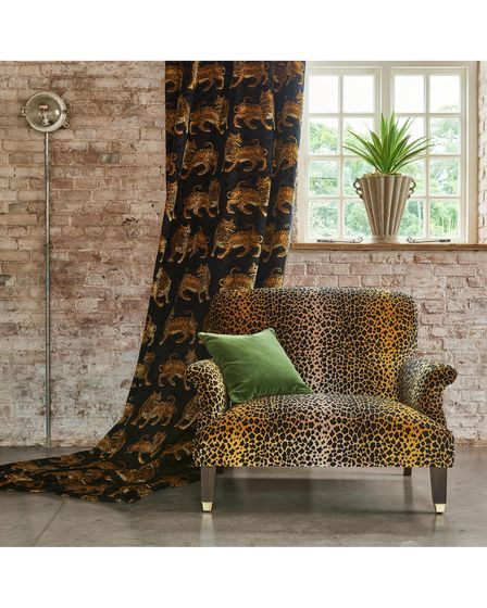 A chair with leopard print and curtains with traditional Indian tigers printed on them, Warner House