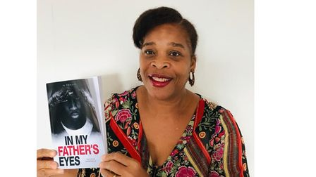 Author Yvonne Phillip with book In My Father's Eyes