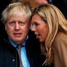 Boris Johnson with his partner Carrie Symonds (R)