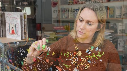 Writer and illustrator Lucy Morris putting together her window display, for her book The Song For Ev