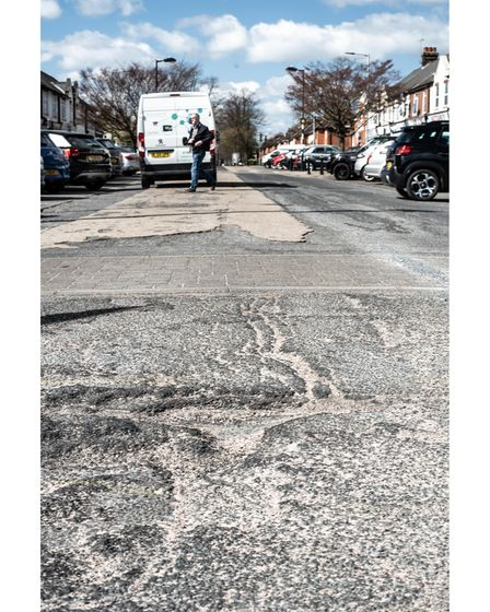 The potholed and damaged road surface in Queen's Way, Ipswich