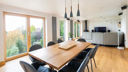 Open-plan dining area with sitting area behind in the eco house in Down Road Portishead. Two sets of French doors on left.