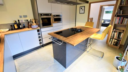 Kitchen in the eco house in Down Road Portishead. Wooden worktops, central island with hob. Cupboards with ovens.