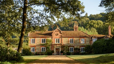 a stately home surrounded by trees in the Surrey Hills