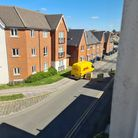 DHL delivery truck driving around the planters on Jovian Way, Ipswich