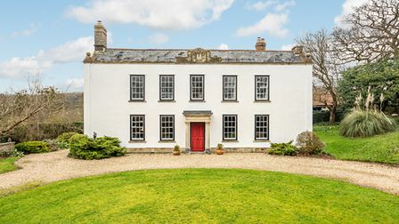 Grade-11 listed white Georgian facade manor house in Christon, Axbridge with lawn and circular driveway.