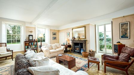 sitting room with white sofas, patterned rugs, windows at the back and French doors on right and fireplace.