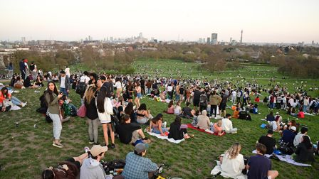 People enjoy the evening sunlight on Primrose Hill, north London. Picture date: Tuesday March 30, 20