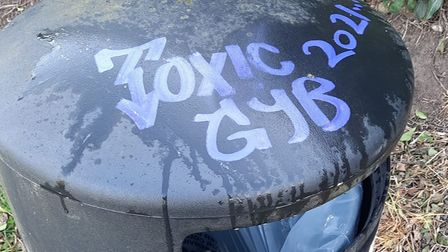 """A public littler bin with """"Toxic GYB 2021"""" scrawled on the top in blue ink."""