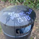 "A public littler bin with ""Toxic GYB 2021"" scrawled on the top in blue ink."