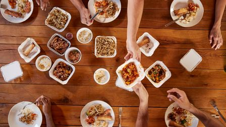 Friends at a table sharing Chinese take-away, overhead view Picture: GETTY IMAGES