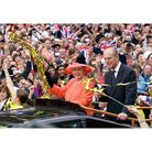 Britain's Queen Elizabeth II and her husband, the Duke of Edinburgh, ride along The Mall in an open-