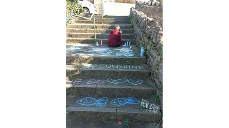 Girl writing message as part of chalk trail
