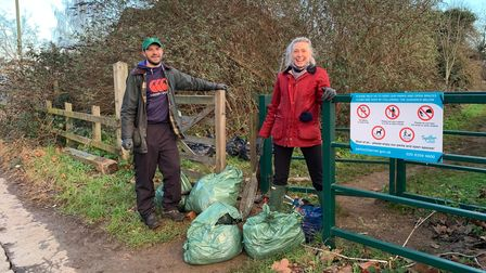 Two people with rubbish from Welsh Harp reservoir