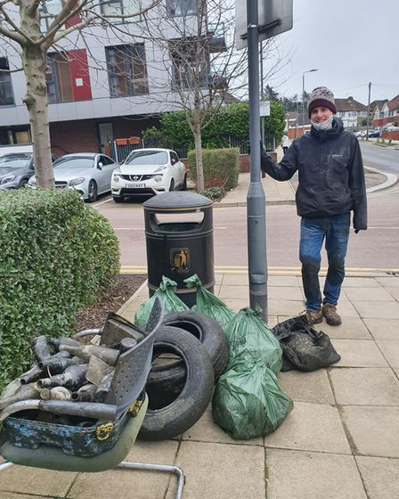 Volunteer next to a bin with rubbish from the Welsh Harp