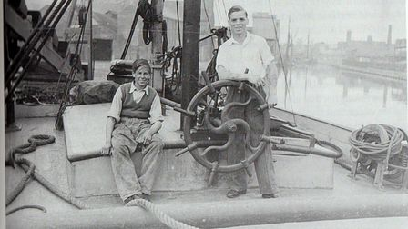Ivan Hazelton at the wheel of a barge in Ipswich
