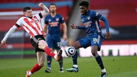 Sheffield United's Oliver Burke (left) and Arsenal's Thomas Partey battle for the ball during the Pr
