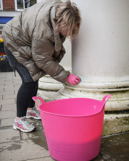A volunteer cleans the columns outside Saffron Walden library for Big Clean Up Day, April 2021