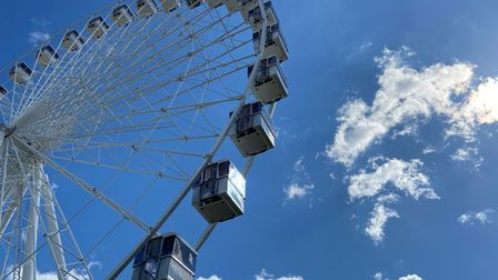 The gondolas of the giant wheel in front a blue sky with bright white clouds