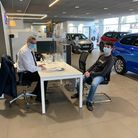 Andrew Poppett welcoming a customer back to Vospers Torbay Peugeot.