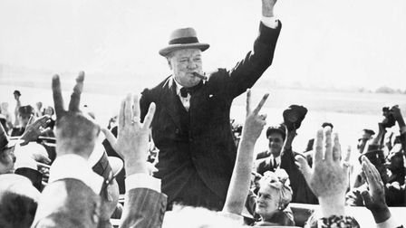Sir Winston Churchill makes the Victory Sign as he greets well-wishers from his automobile. Photogra