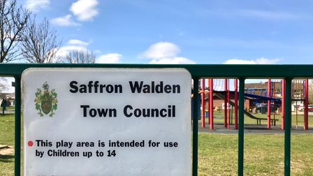 """A sign in front of a playground with a coat of arms: """"Saffron Walden Town Council""""."""