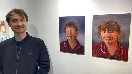 Kyle Ball smiling besides his two portraits of Healthcare Assistants from JPUH