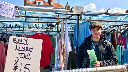 A man stands under a tent filled with clothes on Saffron Walden's Market Square