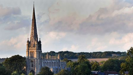Saffron Walden's large church with its tall steeple climbs towards a cloudy sky