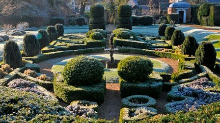 Frosted green hedges form a neat pattern around a central statue in Bridge End Gardens