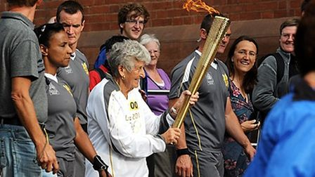 Connie Adam takes over the Olympic torch relay from Norwich Castle.