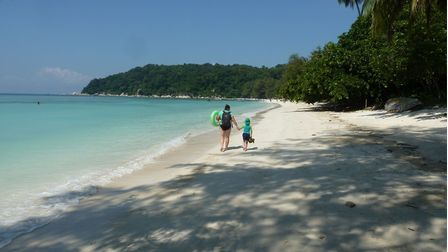 Oscar and his mum on a beach stroll at the Perhentian Islands