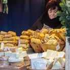 A woman stands behind a market stall laden with different types and sizes of cheese.