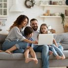 Happy young family with little kids sit on sofa in kitchen have fun using modern laptop together, sm