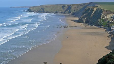 Taken from the cliffs overlooking Watergate Bay, the waves crash onto the sand of an empty beach.