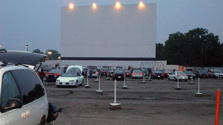 Cars are parked in front of a large outdoor screen, ready for the film to start as night falls.