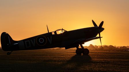 A Spitfire on the airfield at IWM Duxford at sunset.