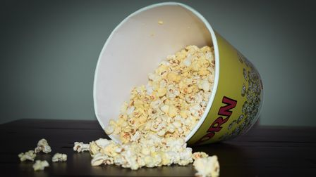 A mostly full, large box of popcorn lies on its side with some pieces scattered around it.