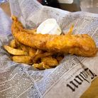 A portion of chips and battered fish sit nestled in old fashioned newspaper.