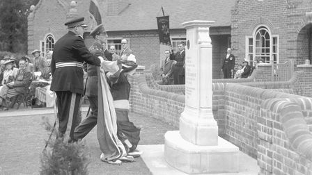 Sir Edmund Bacon placing a flagat the Second World War Memorial Bungalows on Mousehold Lane, Norwich.