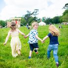 Three children run towards a group of tents in the distance. One is looking back at the camera smiling.