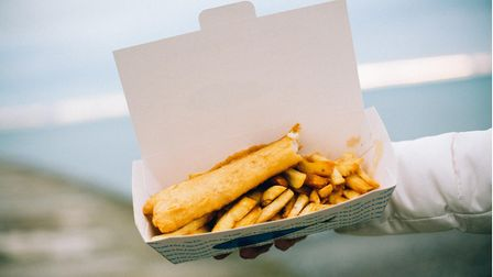 An unseen person holds up a box filled with fish and chips to the camera, a blurred view of the sea behind.