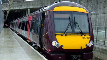 A purple CrossCountry train stands beside a concrete platform.