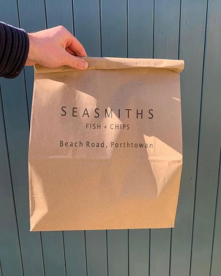 A hand holds out a paper bag marked Seasmiths Fish and Chips